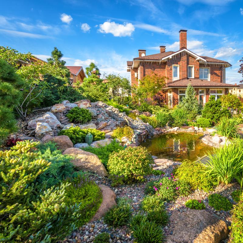 Andscape design of home garden. Beautiful landscaping with small pond. Landscaped place with rocks in summer. Moscow Region - Aug 24, 2019: Landscape design of stock photos