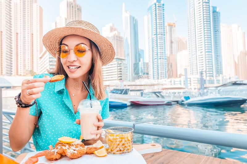 Asian woman eats prawns in batter and French fries on the terrace of a seafood cafe. Happy asian woman eats prawns in batter and French fries on the terrace of a royalty free stock photo