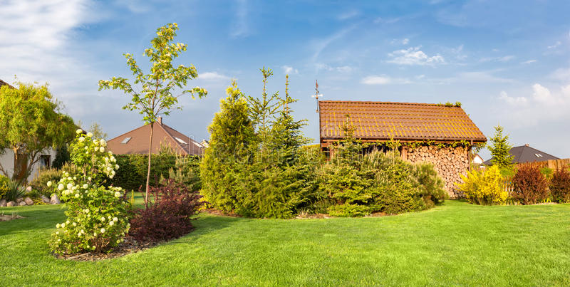 Backyard of a family house. Landscaped garden with green mown grass, wood shelter. Backyard of a family house. Landscaped garden green mown grass, plants and stock image