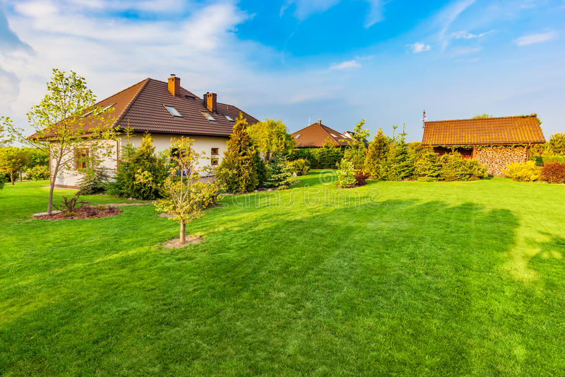 Backyard of a family house. Spacious landscaped garden with green mown grass. Backyard of a family house. Landscaped garden with spacious area of green mown royalty free stock photography