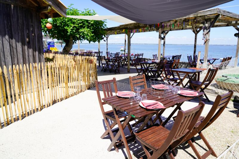 Beach terrace oyster restaurant in seaside with empty chairs and wood table on typical village of l`herbe in Cap Ferret France. A beach terrace oyster restaurant royalty free stock photography
