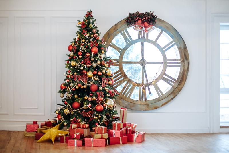 Beautiful Christmas living room with decorated Christmas tree, gifts in front of whate wall. New year tree with red and gold decor royalty free stock photography