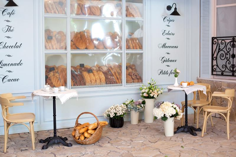 Empty coffee and restaurant terrace with tables and chairs in the French style. Freshly baked pastries, buns and bread in a bakery. Display case. Street cafe stock photos