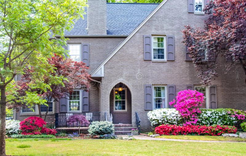 Entrance to grey brick two story house landscaped with Japanese Maples and Azaleas with shutters and a front seating area. stock photos