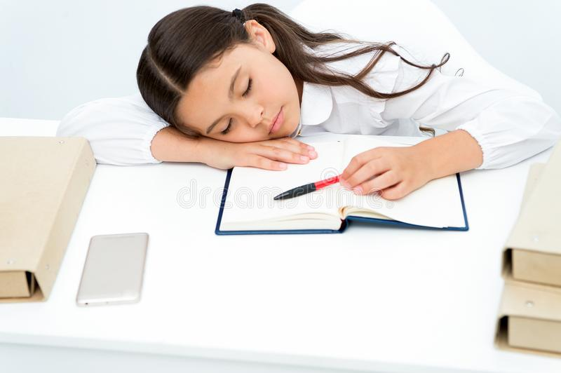 Fall asleep on lesson. Girl child fall asleep while reading book table white background. Schoolgirl tired of studying. And reading book. Kid girl school uniform royalty free stock photo