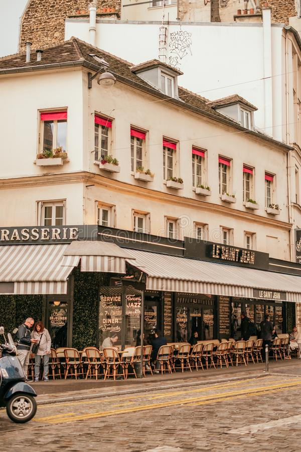 French cafe terrace. Paris, France - April 6, 2019: Charming traditional french cafe with tables on terrace in evening, landmark in Paris stock photography