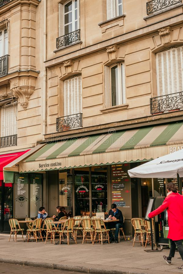 French cafe terrace. Paris, France - April 6, 2019: Charming traditional french cafe with tables on terrace in evening, landmark in Paris royalty free stock image