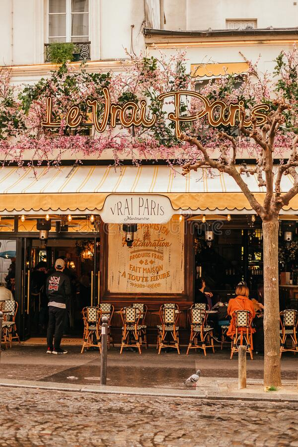 French cafe terrace. Paris, France - April 6, 2019: Charming traditional french cafe with tables on terrace in evening, landmark in Paris stock images