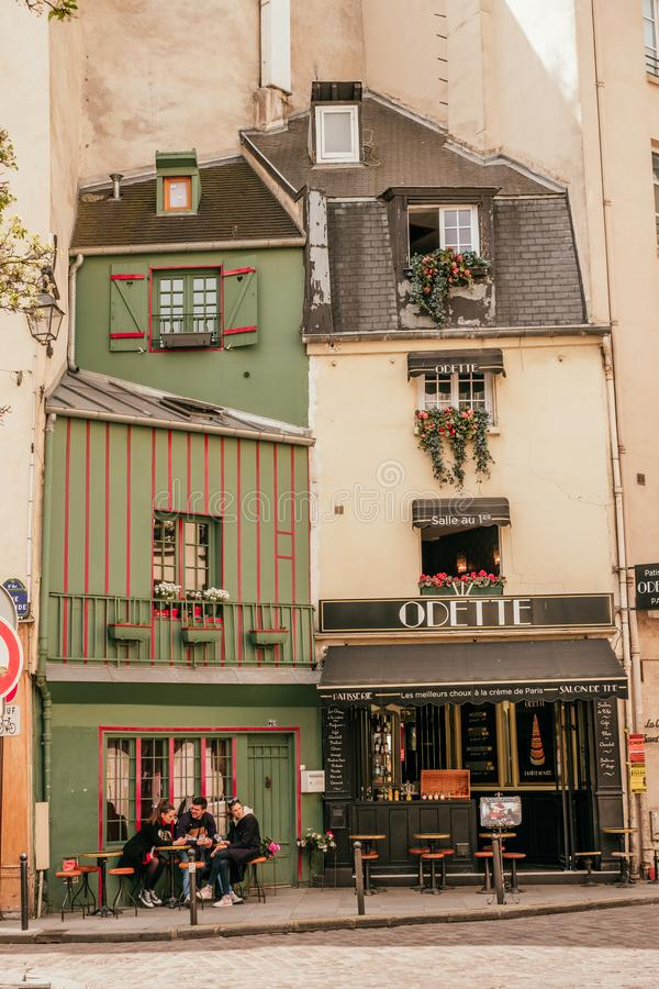French cafe terrace. Paris, France - April 8, 2019: Charming traditional french cafe with tables on terrace, landmark in Paris royalty free stock image