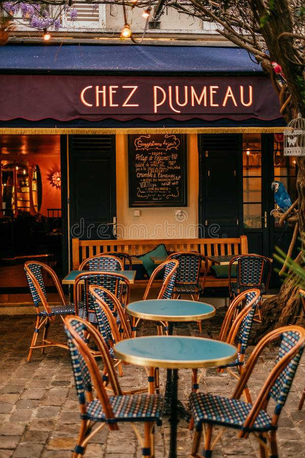 French cafe terrace. Paris, France - April 9, 2019: Charming traditional french cafe with tables on terrace, landmark in Paris stock photography