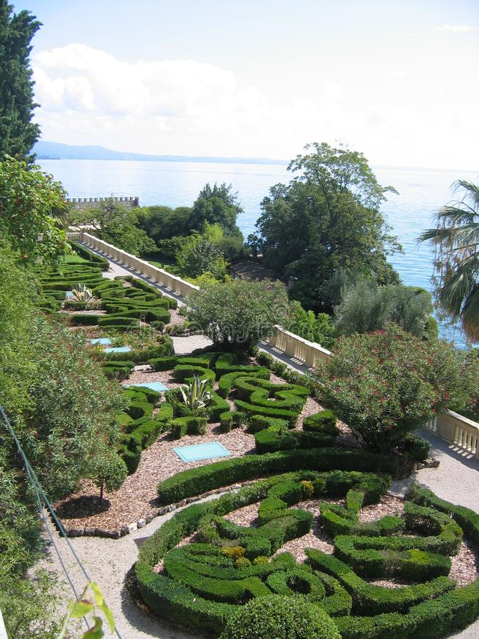 French garden in terrace on the lake of Garda in Italy. Travel destination. Blue lake. Blue sky with clouds. Sunny day. Multiform of trees. Differente kind of royalty free stock images