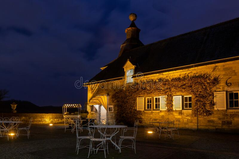 French looking and feeling terrace in Neercanne at the Dutch - Belgium border during blue hour. French looking and feeling terrace near the entrance of chateau royalty free stock photos