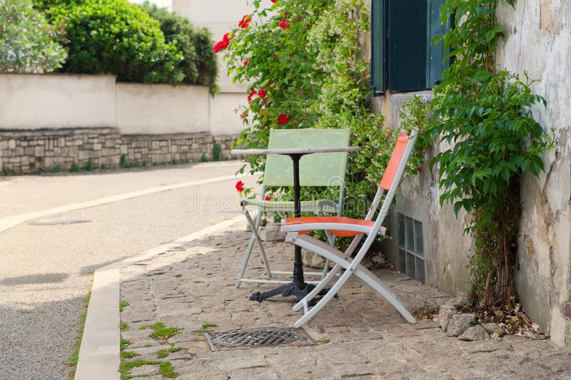 French terrace outdoor. Romantic French terrace with colorful bistro set and red roses stock photo