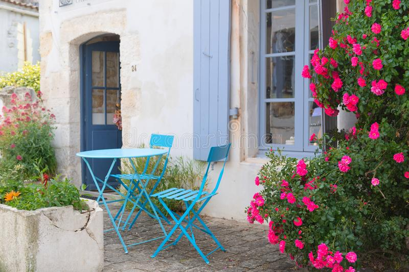 French terrace outdoor. Romantic French terrace with blue bistro set and pink roses royalty free stock photo