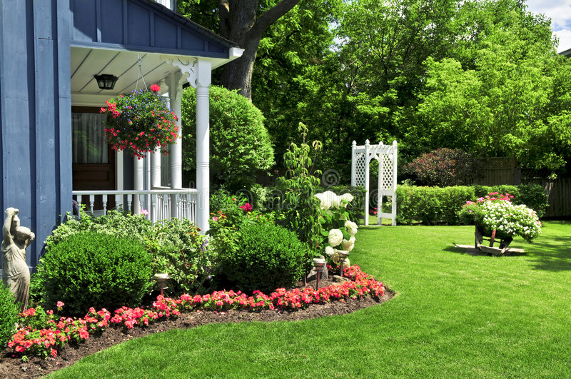 Front yard of a house. Landscaped front yard of a house with flowers and green lawn royalty free stock images