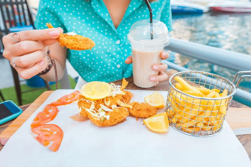Girl eats prawns in batter and French fries on the terrace of a sea cafe. A girl eats prawns in batter and French fries on the terrace of a sea cafe stock photos