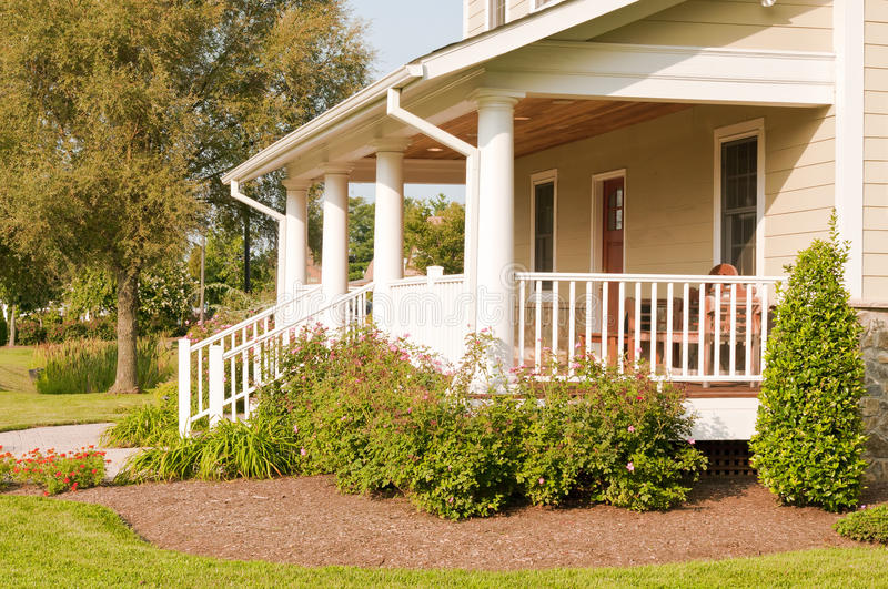 Landscaped house porch. A modest suburban house with a large white porch and landscaping stock photography