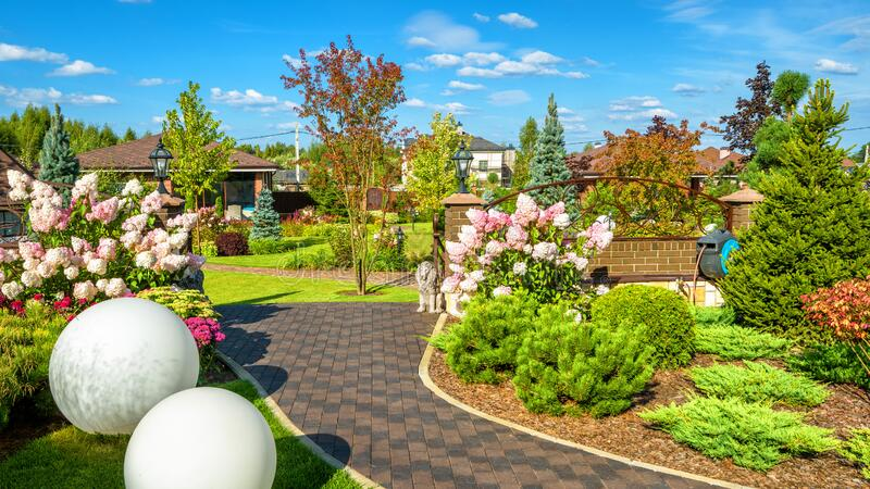Landscape design at residential house. Beautiful landscaping in home garden. Panoramic view of nice landscaped garden in backyard. Moscow Region - Aug 24, 2019 royalty free stock photography