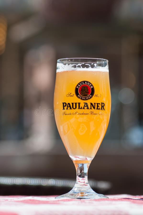 Closeup of glass of french beer from Paulaner` brand at restaurant terrace. Mulhouse - France - 23 May 2019 - Closeup of glass of french beer from Paulaner` royalty free stock photo