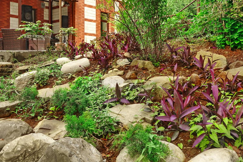 Natural Stone Landscaping. Backyard Decorative Garden. House Terrace With Furniture. Ornamental Backyard Garden With Small Hill, Tropical Plants, Flowers And stock photos