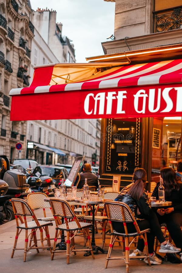 French cafe terrace. Paris, France - April 6, 2019: Charming traditional french cafe with tables on terrace, landmark in Paris royalty free stock image