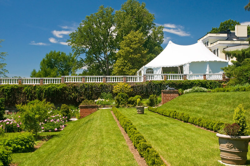Party tent and garden. Large white party tent set up on a front lawn of a luxury mansion, overlooking an elaborate garden stock photography