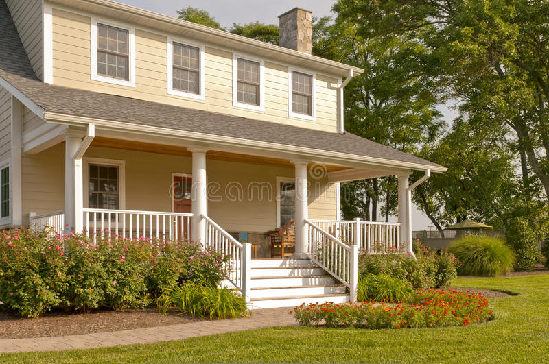 Suburban house with white porch. A view of a modest suburban house with a large white porch, colorful summer flowers and landscaping stock photography