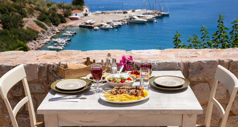 A table served for two with chicken souvlaki and french fries, greek salad, snacks and drinks on the summer terrace of the hotel r. A table served for two with royalty free stock images