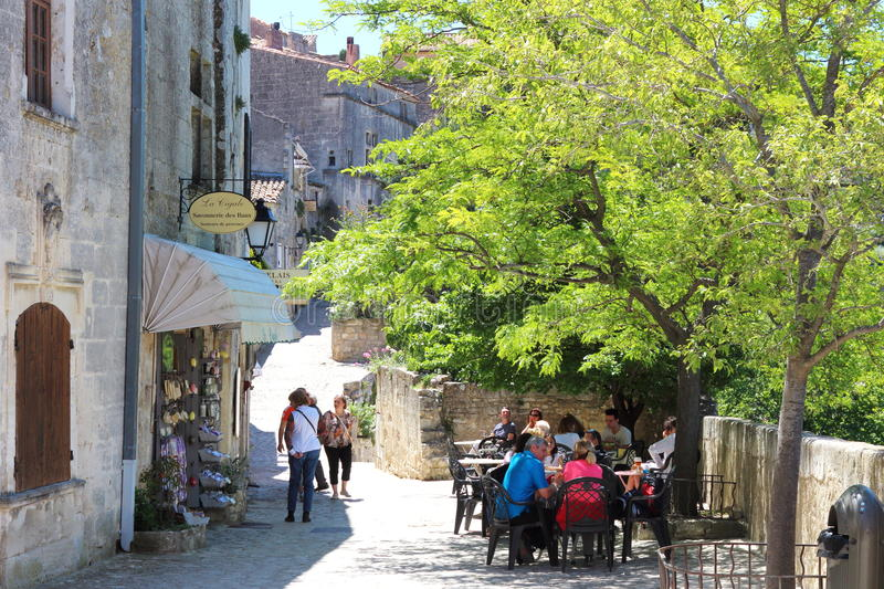 Terrace and soapshop in Les Baux-de-Provence, France. Relaxing people at terrace and a touristic soap shop in a sunny village of Baux de Provence, France, a royalty free stock photography