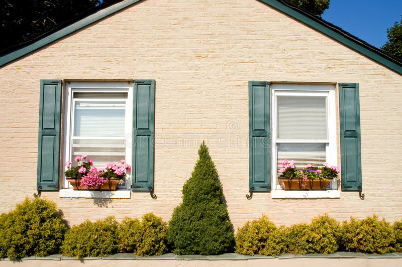 Tiny cottage with flower boxes. The front side of a small but neat cottage or bungalow with nice landscaping and pretty window flower boxes royalty free stock images
