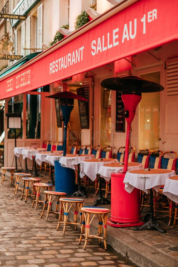 Traditional french cafe with tables on terrace. Paris, France - April 6, 2019: Charming traditional french cafe with tables on terrace in evening, landmark in royalty free stock photo