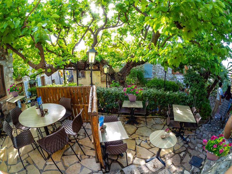 Historic restaurant terrace in Eze village, France. Traditional restaurant terrace inside Eze village with tables and chairs among vintage house architecture, in royalty free stock photos