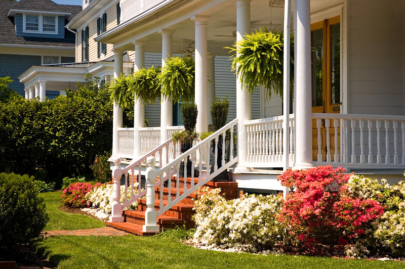 White Victorian porch. A view of a large, white, Victorian-era porch and steps to an old house with colorful spring flowers and landscaping stock photography