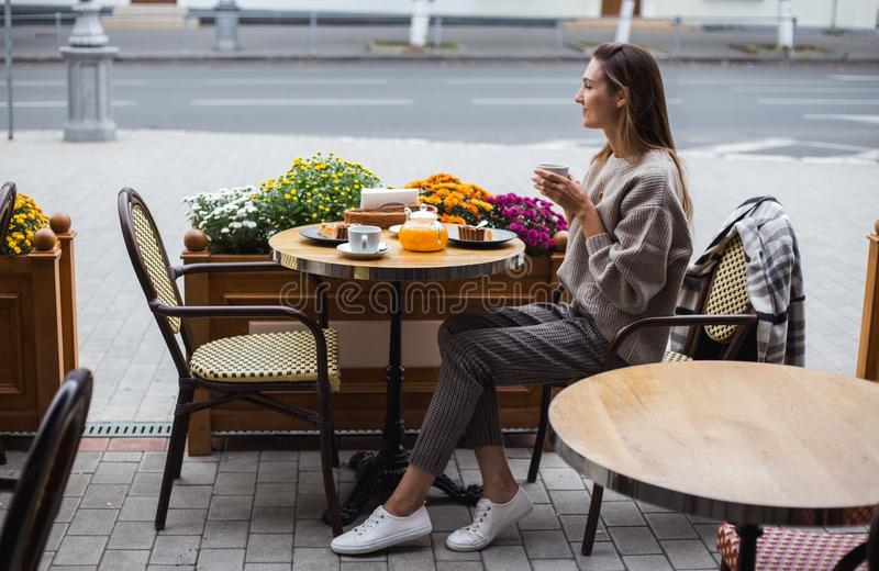 Young stylish woman having a french breakfast with coffee and cake sitting at the cafe terrace. Young stylish woman having a french breakfast with coffee and pie stock images